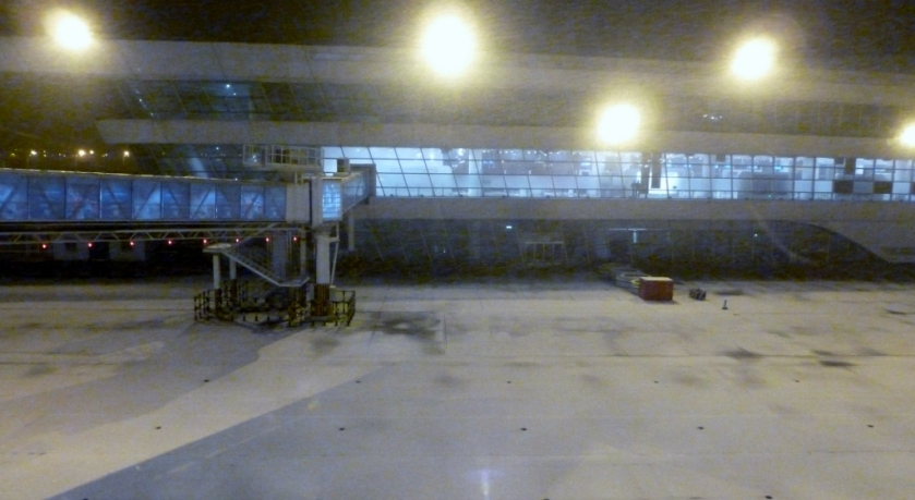 Snow is falling.  Jetway is in place on the left.