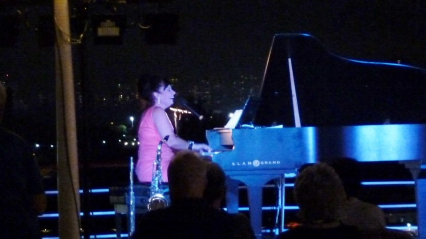 Debby Bacon playing under the stars and before the night lights of Singapore!