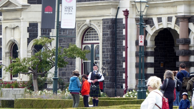 A bagpiper playing in front of the train station.